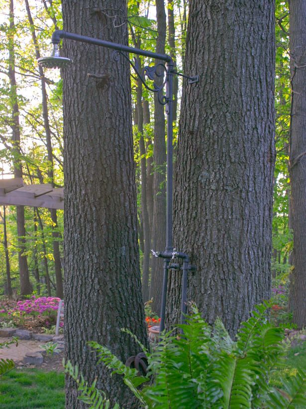 The plumbing for this minimalist shower attaches directly to a tree for  a romantic, woodsy feel.