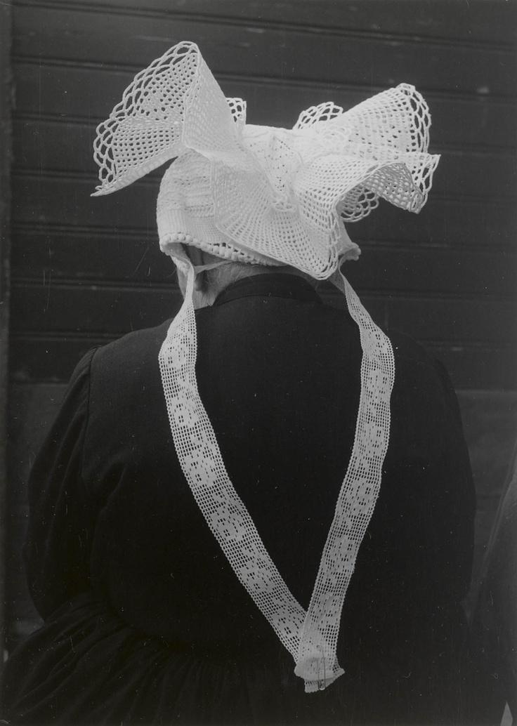 Weduwe Beurkens uit St. Philipsland (93 jaar) met 'haakmuts'. Onder deze gehaakte muts draagt zij een oorijzer met 'getorste krullen' (van getorst vierkant gouddraad). De slippen aan de achterzijde van de muts zijn gemaakt van machinaal vervaardigde slooptussenzetsels. Vroeger werden deze slippen gehaakt.