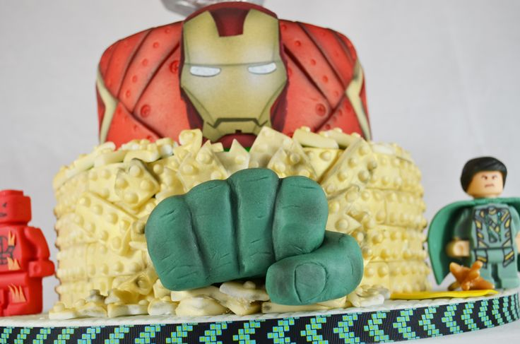 Marvel Super Hero Lego Cake , Hulk's hand comes out of first tier, Iron Man gumpaste faceplate and armor on second tier http://www.sweettierscakery.com/#!Marvel-Super-Hero-Lego-Cake/zoom/c18h4/image1o91