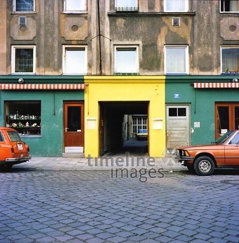 Bunte Ladenzeile in München, um 1978 Zeitlmeir/Timeline Images #bunt #farbenfroh #grün #gelb #rot #Gebäude #Ladenzeile #München #Bayern #70er #Auto #Oldtimer #Geschäfte #Straße #Asphalt
