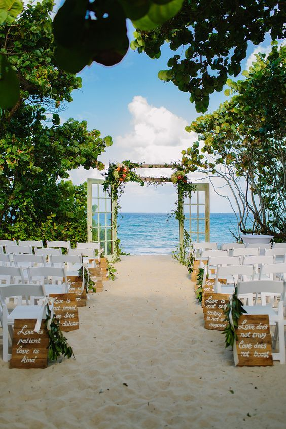 beach wedding ceremony with door arch and wooden aisle marker signs