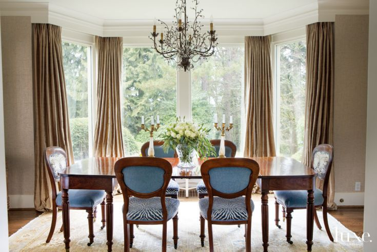 At both ends of a circa 1810 dining table are 1890s chairs with Mulberry Home silk backs and Schumacher velvet seats. The side chairs sport an animal print by Designers Guild on their seats. A Currey & Company chandelier hangs above, while underfoot is a carpet from Kush Handmade Rugs. The drapery fabric is Fabricut.