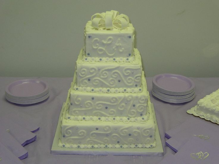 "Lynch wedding - This is a 12"", 10"", 8"", and 6"" square wedding cake covered in white buttercream with white buttercream scrolls and monogram.  The lavender and violet flowers are fondant, as is the bow topper."