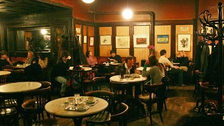 Dansuri  Hawelka  - O cafenea literară din Viena -  Îngeri şi diavoli stau în jurul unui cazan de aur, fierb împreună idei.  Nu sunt nici îngeri, nici diavoli: unul a omprumutat ochelarii lui Brecht, altul aripile lui Icar, altul a împrumutat pletele unei femei (care a rămas cheală, acasă în pod). Eu am împrumutat uzate mănuşi de radiolog.  O, dragi îngeri şi diavoli! Mai există timp pentru plâns? Mai există timp pentru discuţii despre lalele sau iepuri?  Şi iată, a sosit dimineaţa comandată…