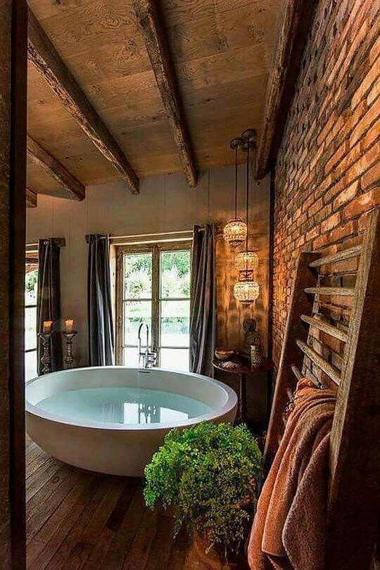 barn wood flooring and ceiling exposed brick wall round bathtub in a great rustic bathroom