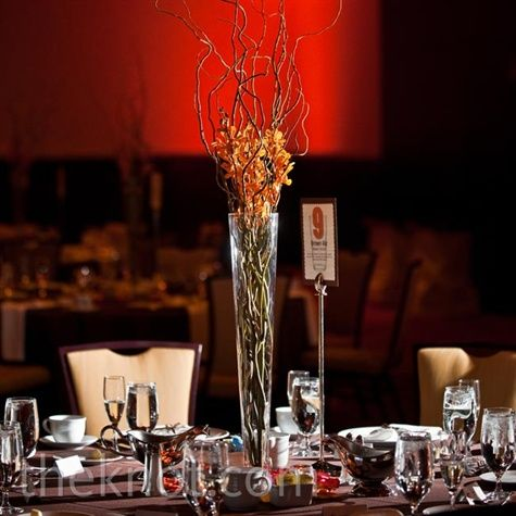 Tall, thin vases filled with curly willow branches and orange orchids topped the reception tables.