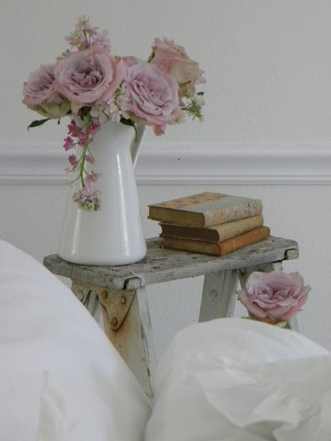 Rustic  ladder top with enamelware, old books and dusty violet roses in a white room