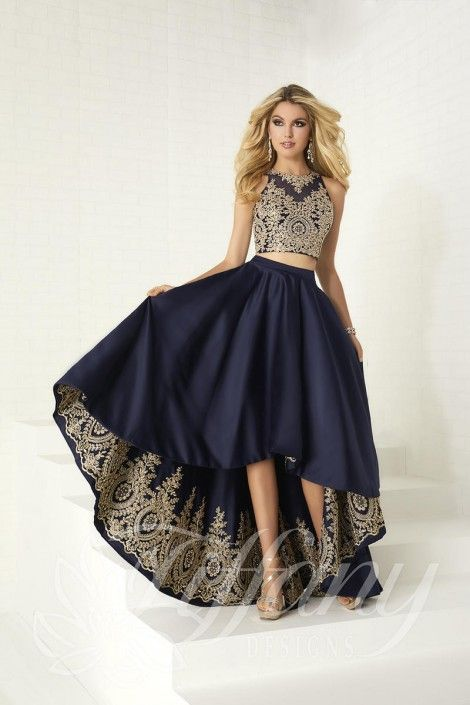 ca46b83f8a0d Style 16305 from Tiffany Designs is a two-piece high low prom dress with a  sleeveless illusion high neck crop top in a metallic embroidered lace design  and ...
