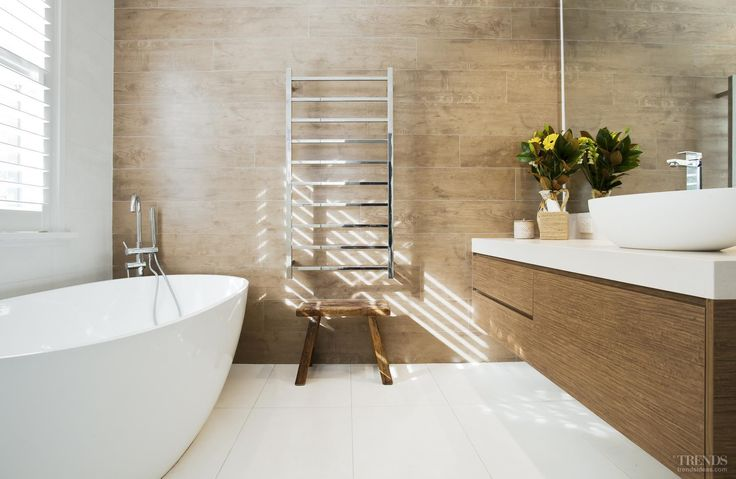Contemporary bathroom addition has timber-look tile feature wall