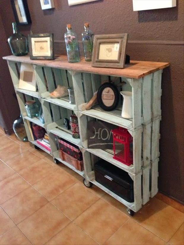 Wood crates assembled into a storage shelf system, add wheels, a wood plank top, and fun paint