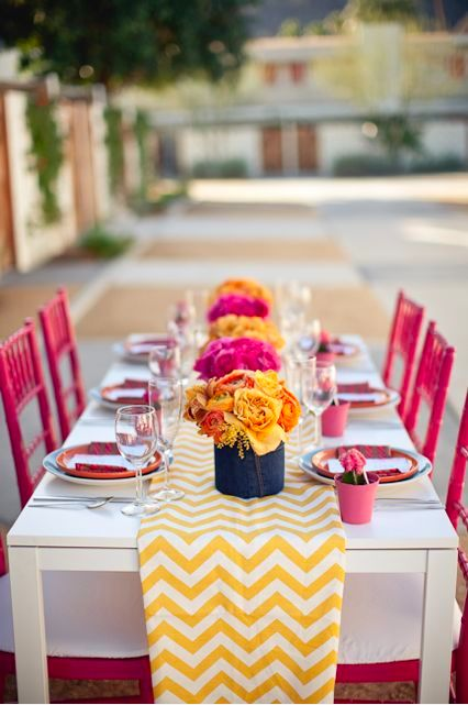 Again, I love the chevron table runner combined with the pink and yellow flowers that correspond to the pink chairs. This table setting is very unified and cute.