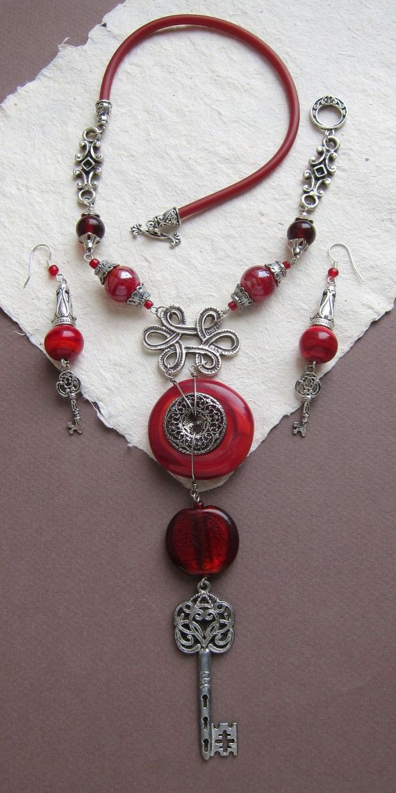 This unique boho necklace handcrafted from exclusive lampwork and Tibetan silver elements such as key pendant and button and also red handmade glassbeads. Rear part - silicone cord.  Вright noticeable red necklace will catches the eyes and attracts all the attention to you!  Necklace length 47 cm (18 1 2), suspension length 16 cm (6 1 2) 47 cm, earrings 8 cm (3)