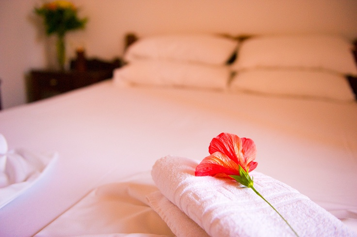 An orange flower on a towel on a bed of the Oscar Suites & Village. More info at http://www.oscarvillage.com/accommodation-two-bedroom-suites