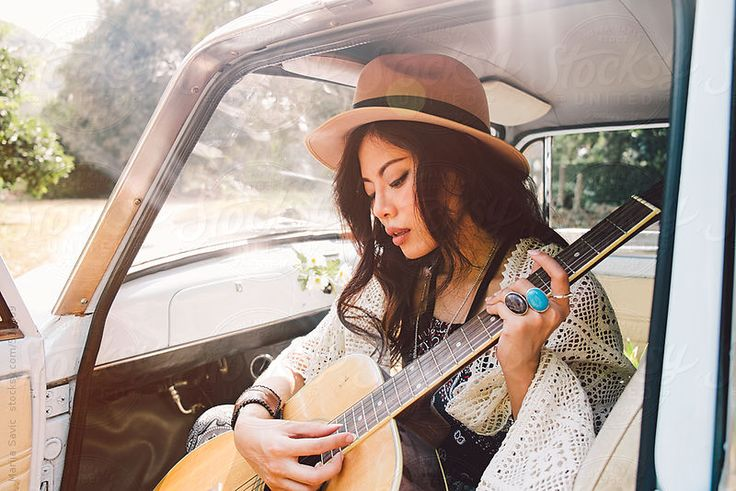 Young Asian woman sitting in a car with guitar.