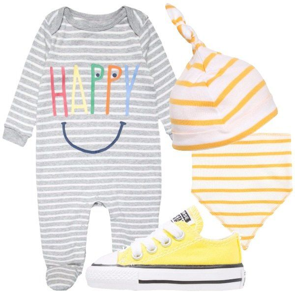 Un neonato che sprigiona felicità: tutina a righe bianche e grigie con stampa, cappellino a righe bianche e gialle, bavaglino a righe bianche e gialle e sneakers gialle, Converse.
