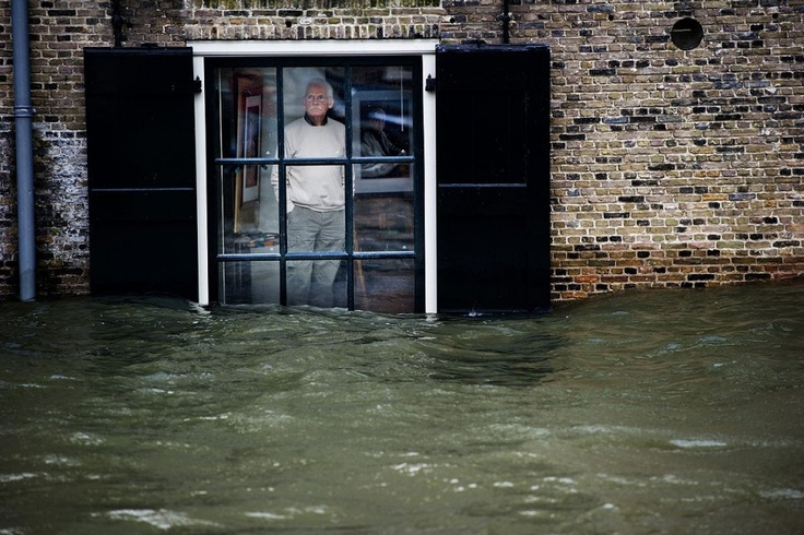 HET IS OOK WEL EENS HOOG WATER IN DE HAVENS VAN DORDRECHT  Jan. 5, 2012  Dordrecht, Netherlands  A man watches flood waters rush past his house window in Dordrecht.  Gale force winds reaching up to 70 miles per hour, as well as heavy rains, are expected along the Dutch coast, which sits below sea level.