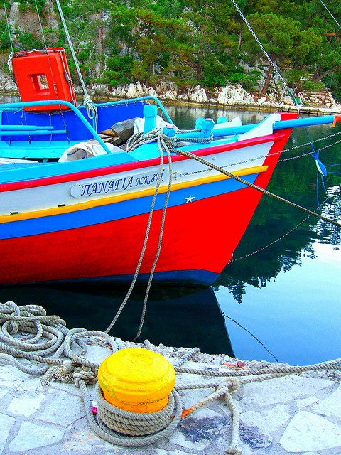 Multi-colored fishing boat anchored at yellow bollard in green surroundings on Paxos island #Ionian #kitsakis