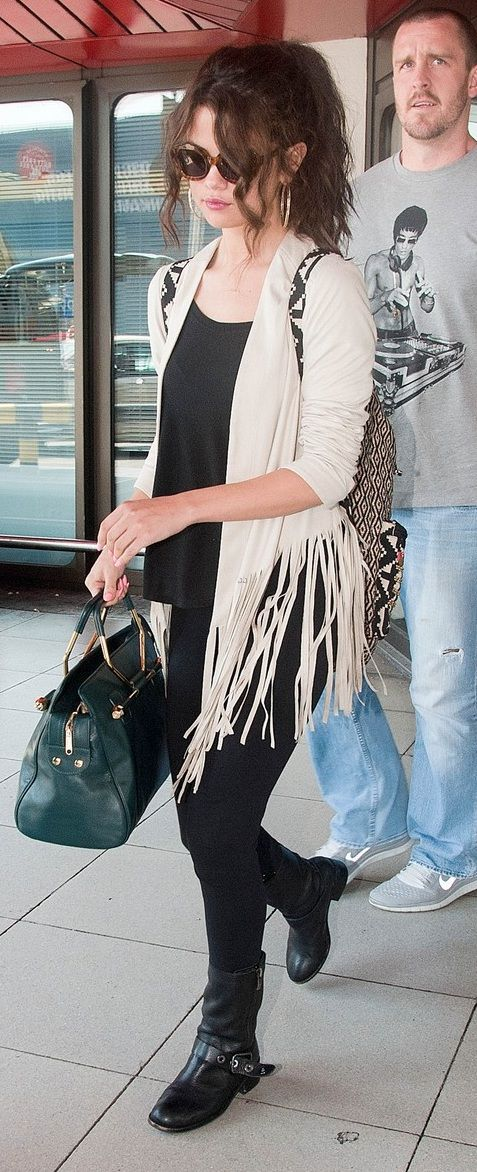 Selena Gomez in a cute fringe shirt paired with a cool dark green handbag & black boots....