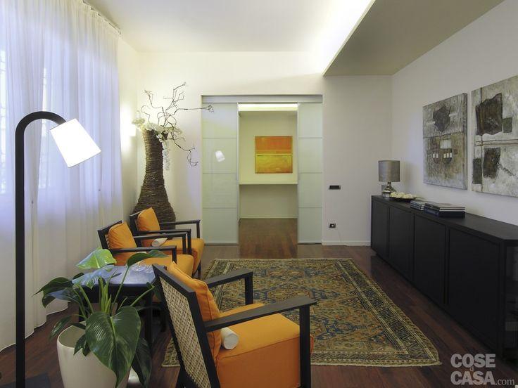 Una porta scorrevole interno muro formata da un doppio pannello vetrato separa l'ingresso dal soggiorno, che si apre con una zona conversazione e lettura arredata con gusto etnochic
