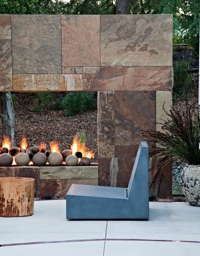 Natural Stone See Through Fireplace Rustic Timber Stool And Modern Chair Makes This An Outdoor