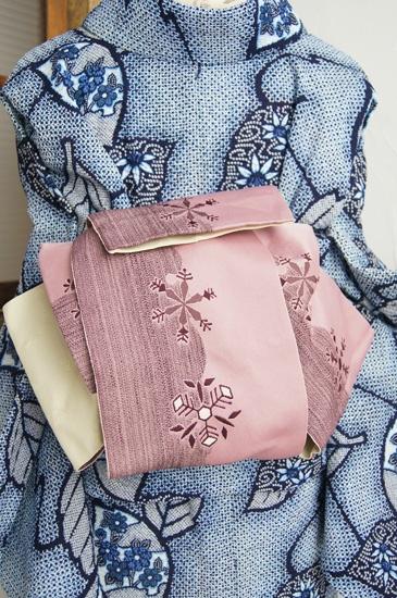 ほのかに淡い紫をおびたスモークがかったローズピンク色も美しく、大胆な雪輪のボーダーに重なるように織り出された雪の結晶のモチーフがロマンチックな物語をつむぎだしてくれる半幅帯です。