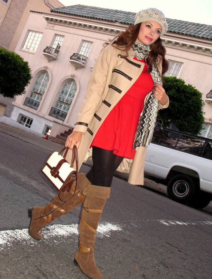 Nicole Bernardes wearing a pair of brown suded over the knee boots paired with a red dress and a matching beige coat.