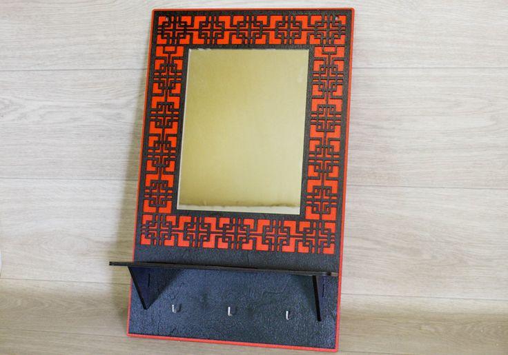 Полка с зеркалом в китайском стиле выполнена из березовой фанеры. Размеры изделия в высоту 55 см, в длину 34 см, в ширину 12,5 см. Полка окрашена водоэмульсионной краской в красный и черный цвет. Внизу полочка имеет три крючка для полотенец. Изделие отлично впишется в интерьер ванной комнаты в восточном стиле.