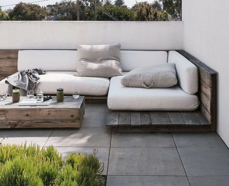 canapé d'angle en palettes grisâtres sur la terrasse