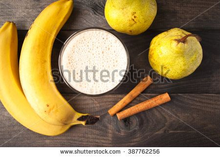 Glass of smoothie, cinnamon sticks, fresh bananas and pears on wooden background. Top view