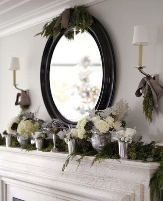Mercury glass, green garland, and white roses on a Christmas mantel.