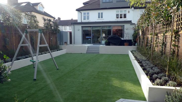 modern sleak garden low maintenance high impact garden design raised white wall beds grey decking east grass lawn turf sunken garden with fire and chimney flat mature trees balham wandsworth london (7)