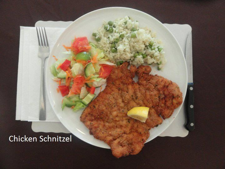 Schnitzels are generally recommended with European hash potato and red cabbage, but here show with alternative choices rice/pea combination and mixed salad: at Savoury and Sweet Restaurant 3770 Bridgewater Street Niagara Falls