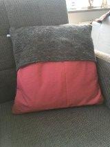 een kussenhoes gemaakt van verhuisdekenstof gecombineerd met een roze stof met groene rondjes.