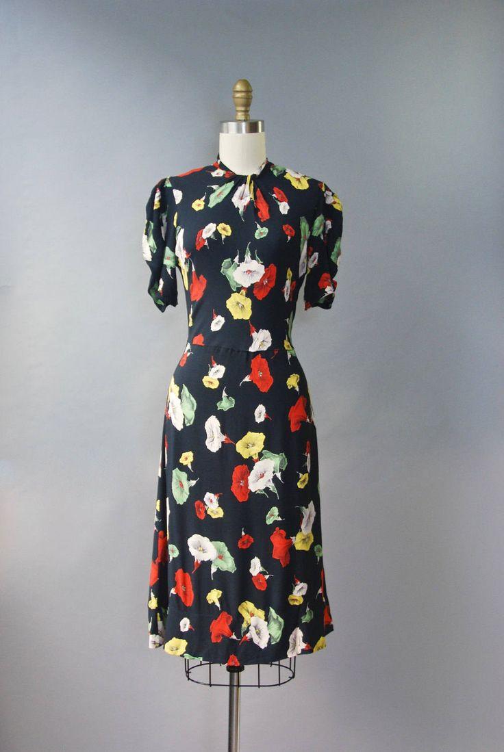 Absoluut prachtige en bijzondere jaren 1940 zwarte rayon jersey jurk met dramatische trompet floral print in rood, geel en groen, puff sleeves, verzamelde hals en knop sluiting op de rug achterkant van de nek. Gewoon mooi!  voorwaarde: er is een klein flard reparatie gedaan aan de kant taille, professioneel gedaan en moeilijk te herkennen. taille naad lijkt een beetje los maar helemaal rond is versterkt. prachtige conditie voor haar leeftijd! vers schoongemaakte en klaar om te dragen Label…