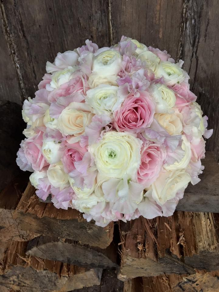 pink and ivory roses with white ranunculus and blush sweetpea, created by lovely bridal blooms