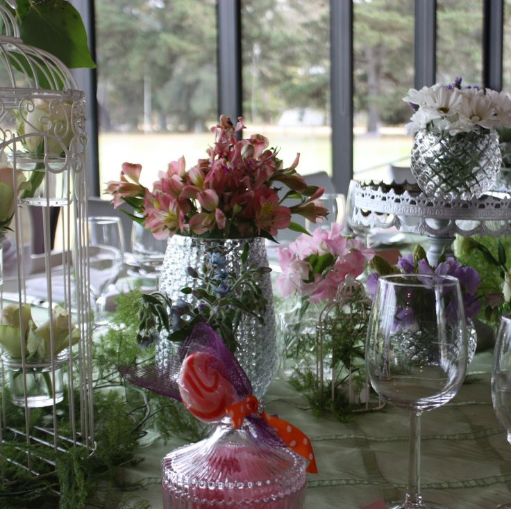 Christening table scape styled with vases filled with roses and foilage. And birdcages filled with daisies. On green
