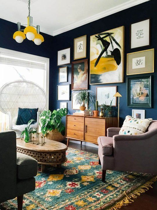 The dark blue walls offer a stunning backdrop for an eclectic wall gallery, picking up the accent yellow in both the light shade and patterned rug.