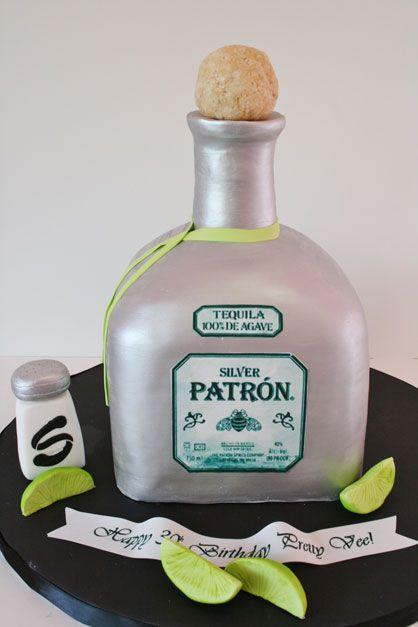 Un pastel en forma de botella de tequila patron junto con su salero y limones.