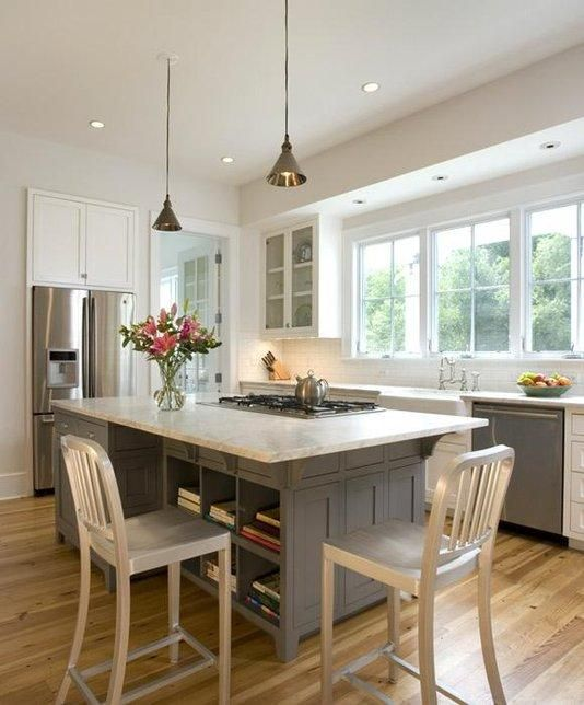 Spacious kitchen with a traditional look but modern painted cabinets and counters. The kitchen features a farm sink and island cooktop with inset cabinet doors and drawer fronts. The desk and seating at the island make this a versatile space for a young family.