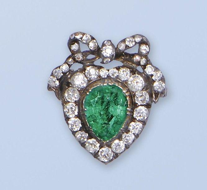 """Pittoresque bague """"sentimentale"""" dite de """"foy"""", en argent 925 millièmes et or 14 k (585 millièmes). Elle est ornée d'une émeraude piriforme dans un pourtour de diamants de taille ancienne. Le décor est surmonté d'un noeud, également serti de diamants de taille ancienne. La bague symbolise l'engagement ou les fiançailles, modèle très en vogue à la fin du XIXème siècle et au début du Xxème siècle. (égrisures sur l'émeraude). Tour de doigt: 52. Poids brut: 3,6 g."""