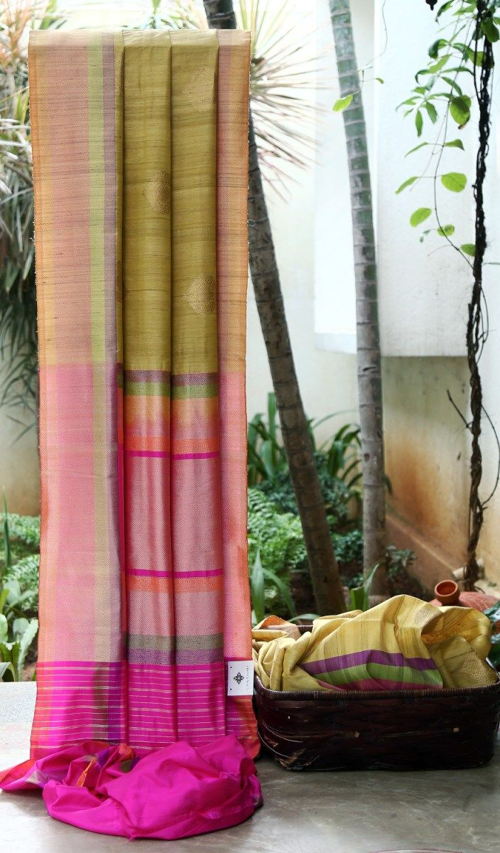 ETHNIC LIGHT GREEN IRIDESCENT MUSTARD YELLOW BENERAS TUSSAR HAS EYE-CATCHING GOLD ZARI MOTIFS RIMMED WITH MULTICOLOUR BORDER WITH INTRICATELY WOVEN GOLDEN ZARI. THE MULTICOLOUR PALLU WITH FUCHSIA P...