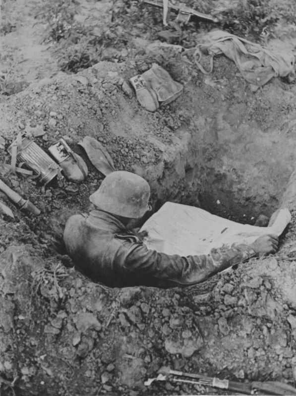 German soldier reading a newspaper in a trench on the Eastern Front