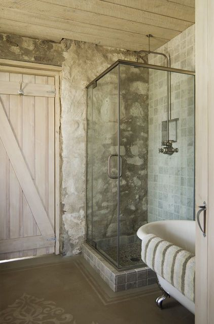Work the new into the old. This modern glass shower disappears into the stone wall. The whitewashed, wide-plank Z door adds softness to this weathered room. Rough wood above is the perfect ceiling choice. Carry the look all the way through every detail with antique hooks and door latches. Keep it honest with exposed plumbing and electrical conduits whenever possible.