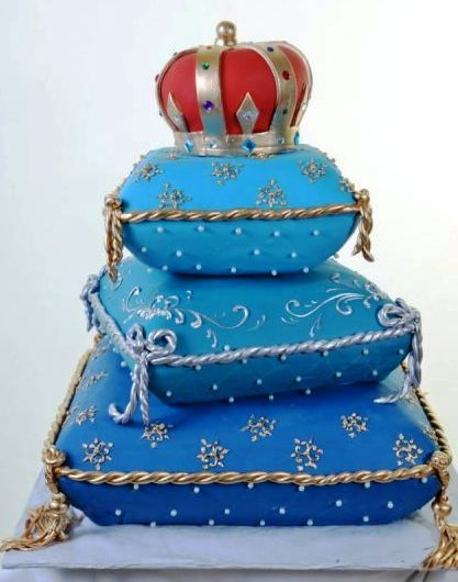 Pastry Palace Las Vegas - Wedding & Specialty Cake #1038 – Royal Pillows. Three tiers of royal pillows that look so real you'll want to rest on them. Silver and gold rope trim and flourishes, topped with a red and gold crown fit for royalty.
