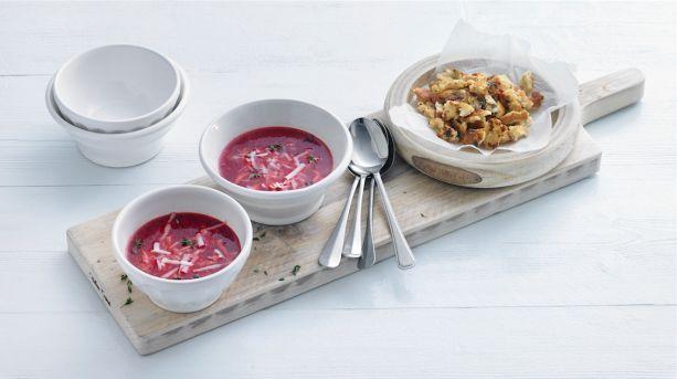 Pittige geitenkaas en zoete rode biet vormen een perfect duo in dit recept voor rode bietensoep. Je kunt de soep 2 dagen van tevoren maken. Soep voorbereiden Snipper 4 sjalotten en snijd 2 tenen knoflook fijn. Was 1 prei en snijd in ringen. Verhit de helft van de boter in een pan met dikke bodem en fruit de sjalot, knoflook, prei, peper en eventueel zout 8 minuten op laag vuur. Groente en croutons bakken Scheur 1 petit beurre brood in stukjes van 1 centimeter. Ris de blaadjes van de takjes…