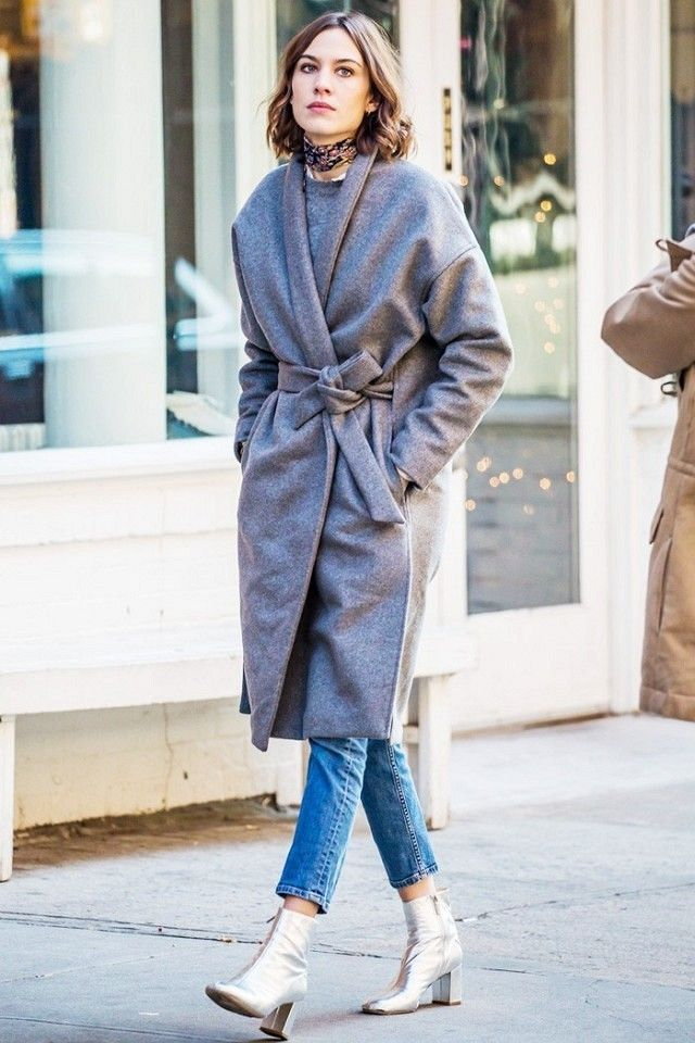 Alexa Chung wears a gray sweater, coat, cropped jeans, metallic boots, and a silk floral scarf