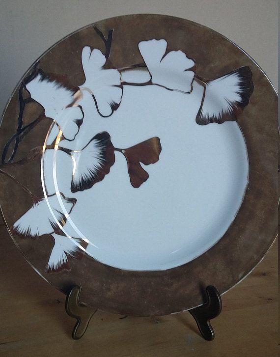 Plaque « Gingko » est peint à la main. Nous avons utilisé l'éclat bronze à plinthe plat pour les fleurs de Ginkgo, nous avons utilisé l'or pur avec la technique du pinceau, produisant des fleurs et autres mélangés, donnant de la légèreté et l'élégance à cette pièce unique. Le plat « Gingko » est un d'une sorte, fabriquée en Italie, fait avec passion et amour. Son succès et offert ce sera incroyable... essayez-le ! Le Taille 32 cm de diamètre