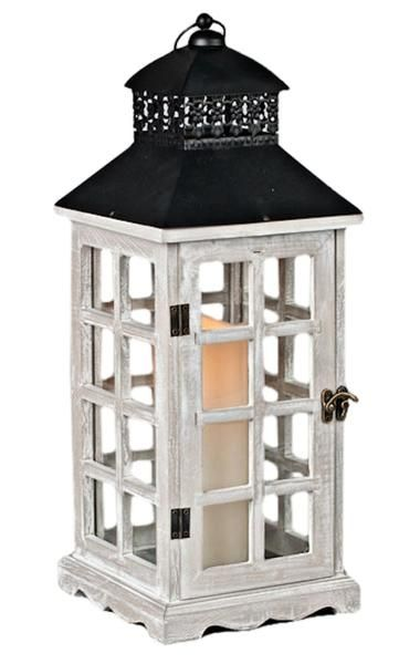 Country rustic wooden lantern has a whitewashed finish with glass panes and a black metal decorative top Beige bisque flameless pillar candle has the look of a