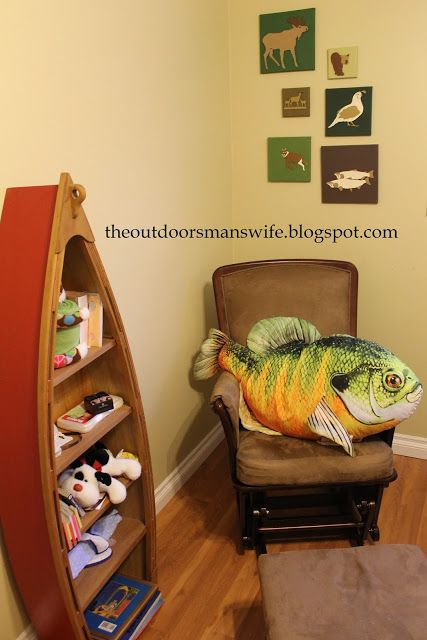 Hunting and outdoors themed nursery with canoe shelf, DIY wall art, and fish nursing pillow