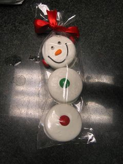 These are chocolate covered oreos in the shape of a snowman wearing earmuffs.  I think it's such a good idea.